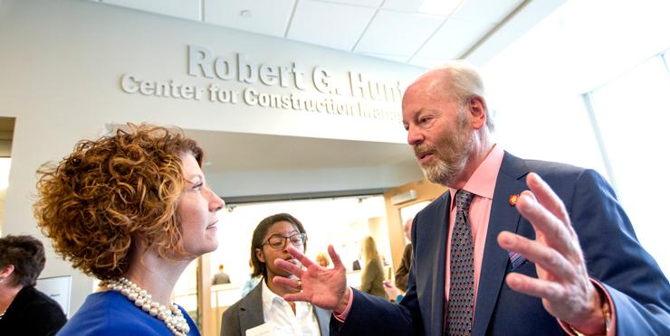 Robert G. Hunt (right) speaks with Jennifer Bott, dean of the Miller College of Business, outside of the new center.