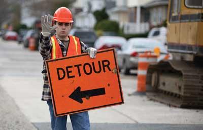 Construction worker holding detour sign