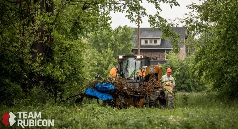 Case track loader clearing brush