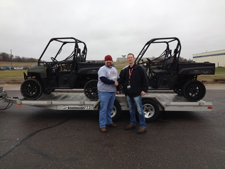 Tom Oestreich, of POlaris Defense, presents a pair of RANGER 800s to Garrett, of Team Rubicon, a non-profit helping to clean up the Washington, Ill. area.