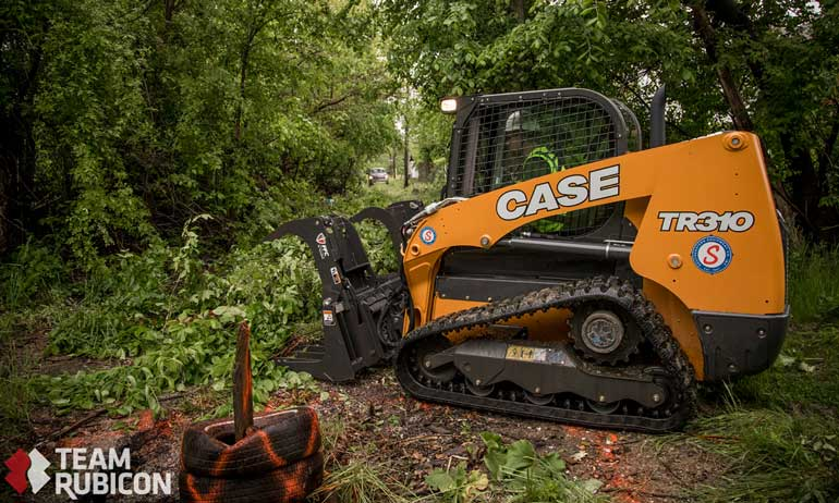 Case track loader clearing brush