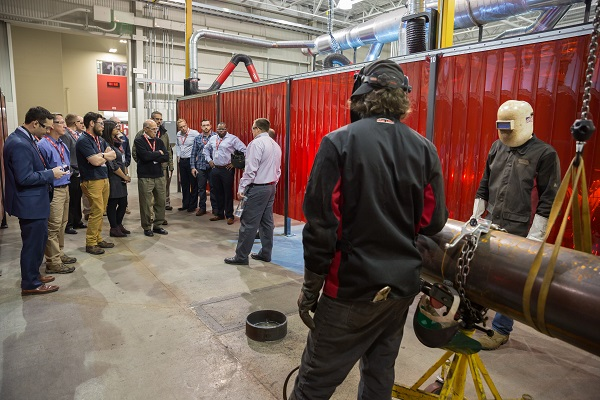 A tour group, including CE contributing editor Brad Kramer, learns about the API section of the Welding Technology & Training Center. Currently the center features 10 API welding booths.