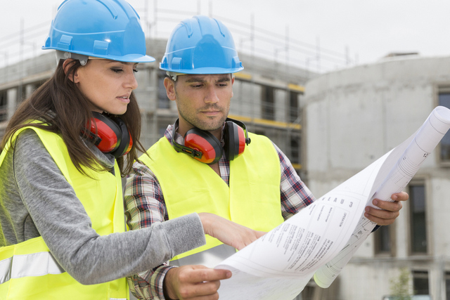 Engineers on building site cheking plans