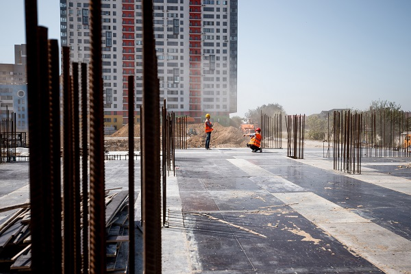 The building site against the background of a multistorey building. Two builders are working .