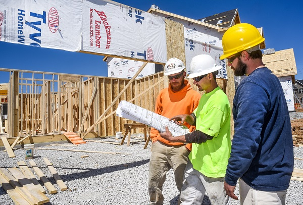 Three male construction workers, carpenters, wearing hardhats look at blueprints at new residential subdivision home building work site