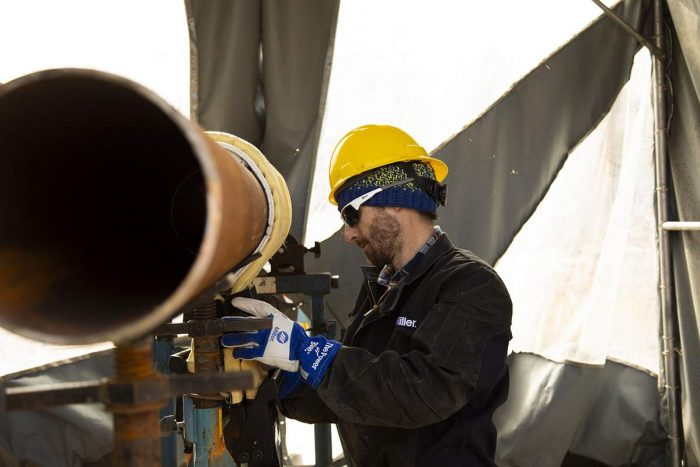 Miller Electric Worker working on a pipeline using induction heating