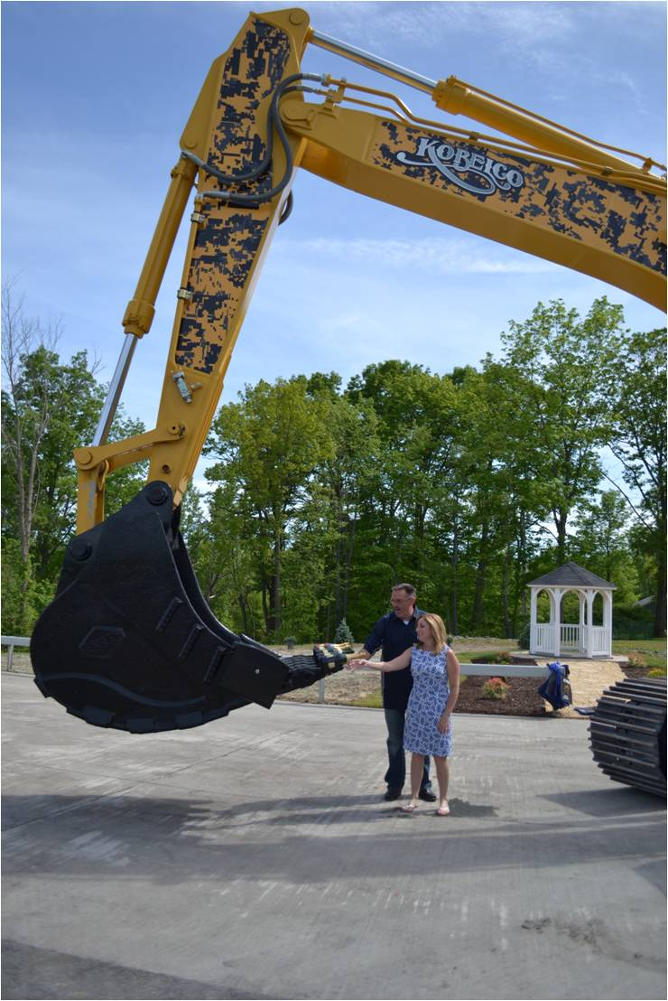 John Finke gets a glass of champagne during the open house event poured from the bucket of a KOBELCO SK350 excavator.