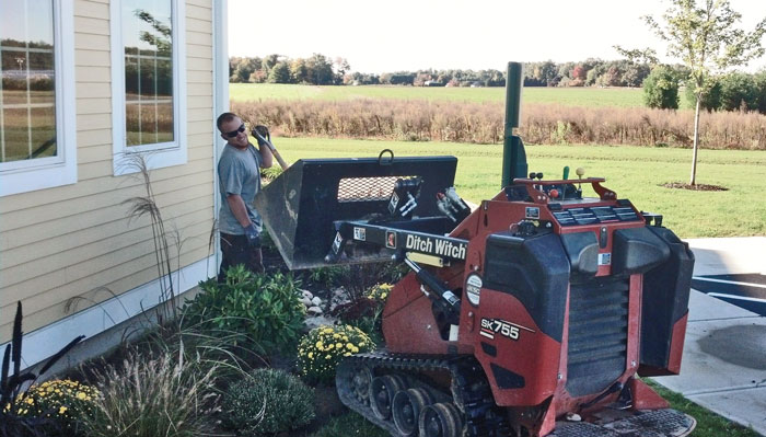In growing and building seasons, Snow & Sons use Ditch Witch SK compact tool carriers with an assortment of attachments, including buckets to bring fresh mulch to newly constructed beds.